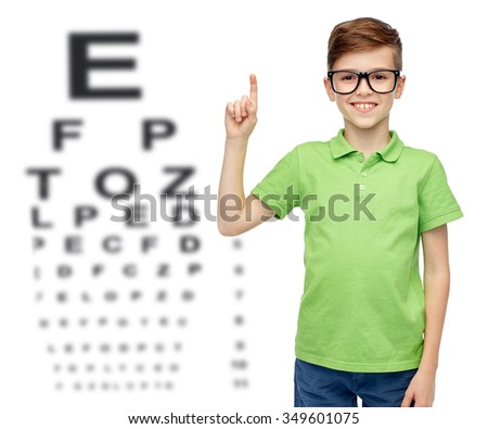 childhood, vision, eyesight and people concept - happy smiling boy in green polo t-shirt in eyeglasses pointing finger up over eye chart background - stock photo