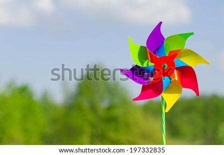 Childish pinwheel against blue sky background. - stock photo