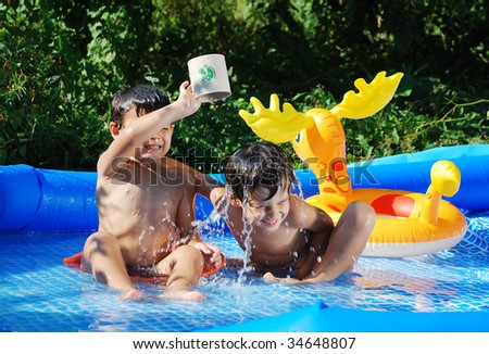 Children activities on swimming pool in summer - stock photo