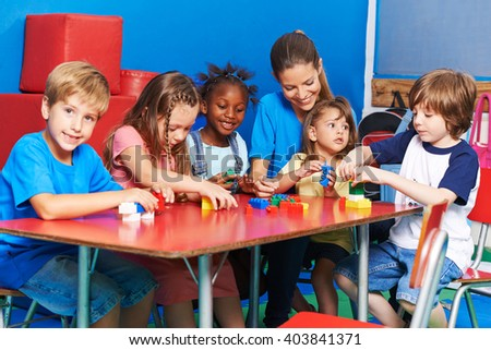 Children an teacher playing with building blocks together in preschool - stock photo