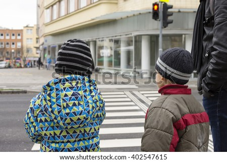 Children and adult waiting at pedestrian crossing for green light.  - stock photo