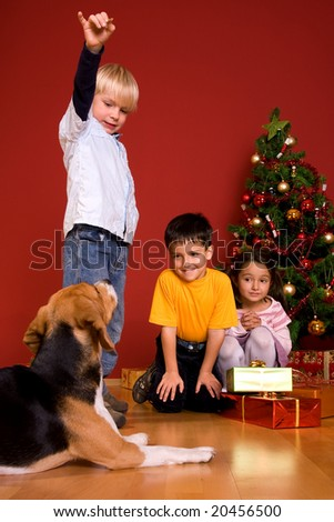 Children and dog by Christmas tree - stock photo