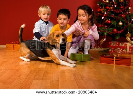 Children and dog sitting by Christmas tree - stock photo