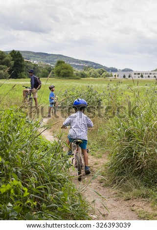 Children and father with bicycles  on a family cycling trip in a country path