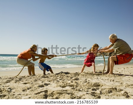 Children and grandparents playing tug of war. - stock photo