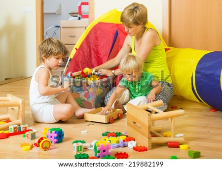 Children and mother collecting toys in plastic box - stock photo