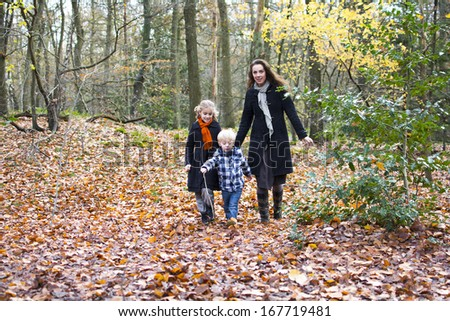Children and mother walking in forest - stock photo