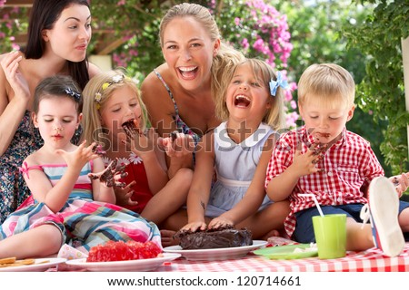 Children And Mothers Eating Jelly And Cake At Outdoor Tea Party - stock photo