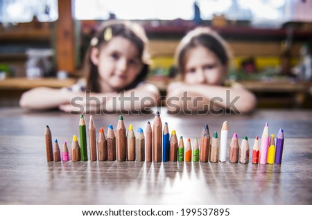 children and pencils lined up in a row - stock photo