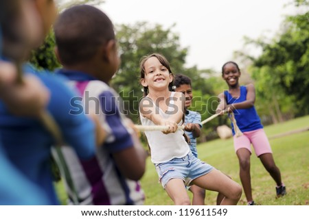 Children and recreation, group of happy multiethnic school kids playing tug-of-war with rope in city park. Summer camp fun - stock photo