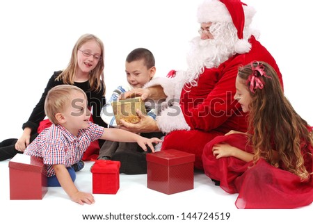 Children and Santa sit on the floor to look at gifts - stock photo