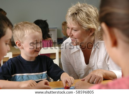 Children and teacher learn while playing a board-game at the preschool class. - stock photo