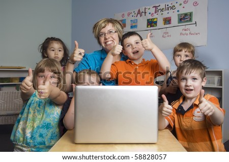 Children and teacher play and learn while using a laptop computer at the preschool class. - stock photo