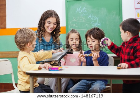 Children and teacher playing with musical instruments in preschool - stock photo