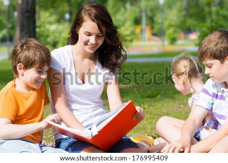 children and teacher reading book together in the summer park - stock photo