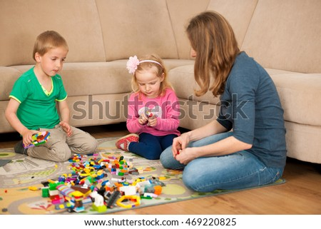 Children and their mother are playing with blocks on the ground