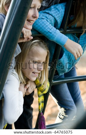 Children (10 and 11 years) leaning on playground equipment, watching and smiling