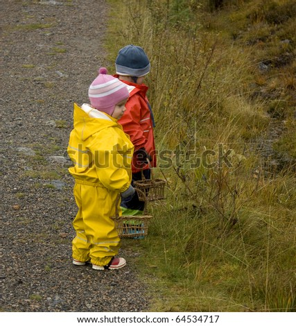 Children (2 and 3 years old) in brightly colored rainclothes, with baskets looking for mushrooms in autumn. - stock photo