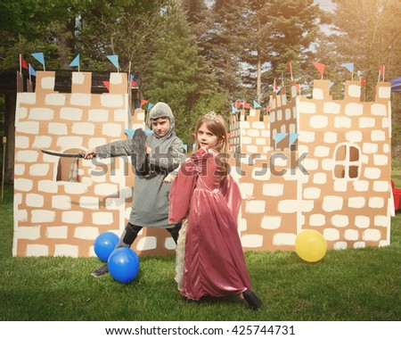 Children are dressed in a knight and princess costume in front of a homemade cardboard castle outside for a creative imagination concept.
