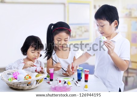 Children are painting easter eggs in art class - stock photo