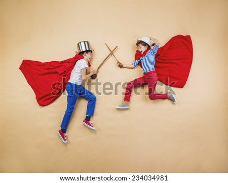 Children are playing as superheroes with red coats - stock photo