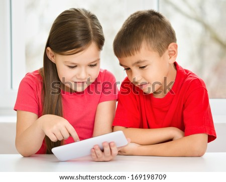 Children are using tablet while sitting at table, isolated over white