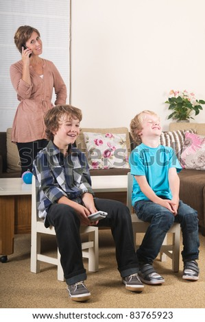 Children are watching tv while mother is calling in the background - stock photo