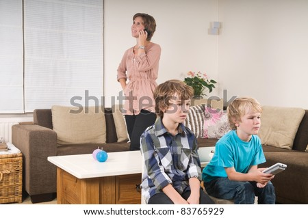 Children are watching tv while mother is calling in the background