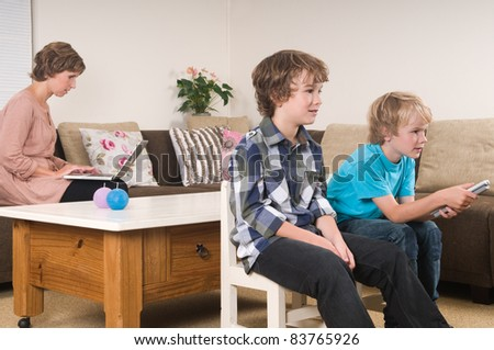 Children are watching tv while mother is working in the background - stock photo