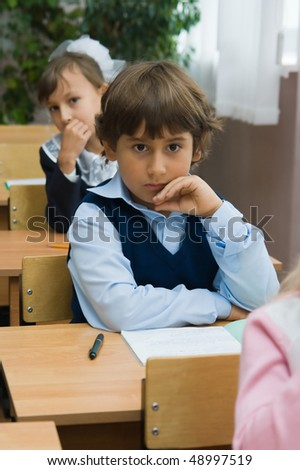 Children at school at a lesson. The thoughtful boy sits at a school desk - stock photo