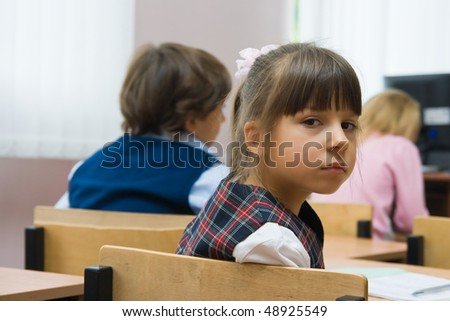 Children at school at a lesson. The thoughtful girl sits at a school desk - stock photo