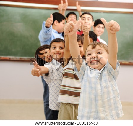 Children at school classroom with thumbs up - stock photo
