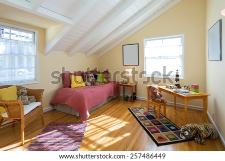 Children bedroom / kids room with beige walls, rug, pillows, bear, peaked roof, toys and view window - stock photo