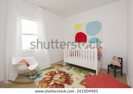 Children bedroom / kids room with light colorful decoration, rug, chair, toddler bed and window. - stock photo