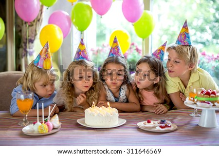 Children blow out the candles on the cake - stock photo