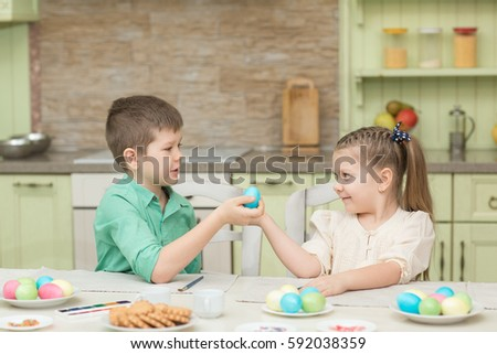 Children boy and girl playing with Easter eggs and laugh