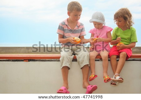 children: boy and two girls sitting on a bench. skin of orange in boy's and little girl's hands - stock photo