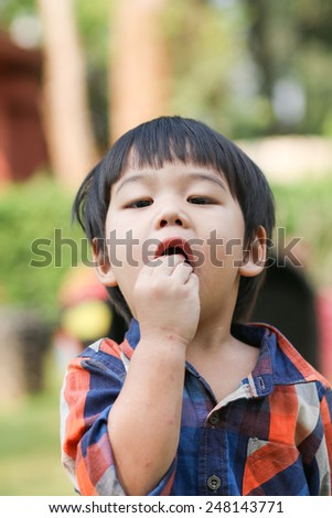 children boy eating chocolate, outdoor nature,