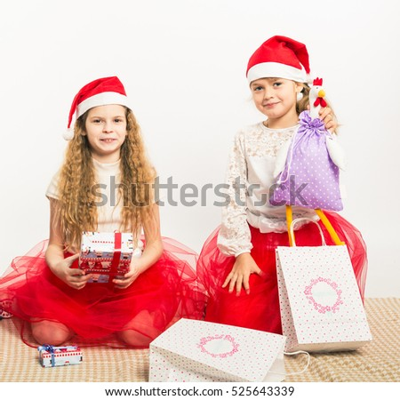 Children (boys and girls) in the New Year clothes open their Christmas gifts. Joy and frustration. On a white background. Mock up. Human. New Year. Christmas.