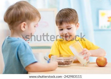 children boys eating healthy food at home or kindergarten - stock photo