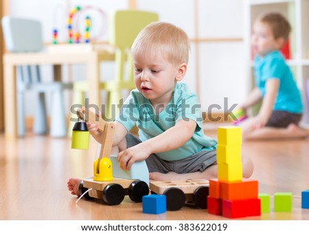 Children boys playing with toy crane in playroom - stock photo