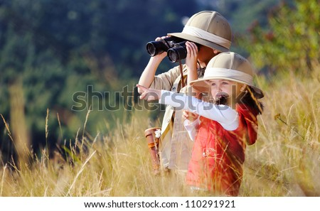 Children brother and sister playing outdoors pretending to be on safari and having fun together with binoculars and hats - stock photo