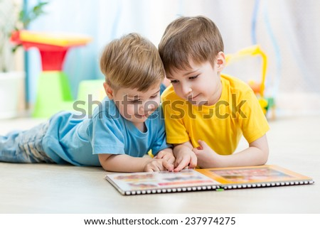 children brothers reading a book on floor indoors - stock photo