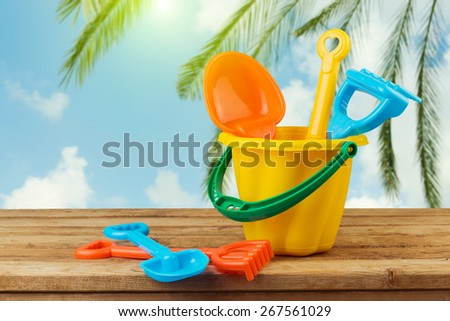 Children bucket and spade on wooden table over palm tree background - stock photo
