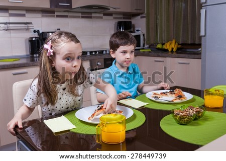 Children captivated by a TV show while eating pizza
