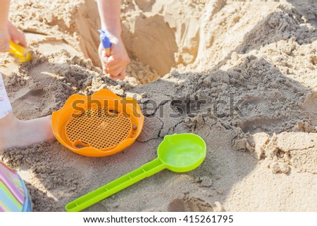 Children carving a hole in the beach sand in a sunny day. - stock photo