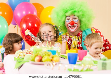 children celebrating birthday party with clown
