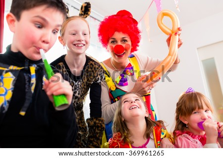 Children celebrating birthday party with noisemakers while a clown is visiting entertaining the kids - stock photo