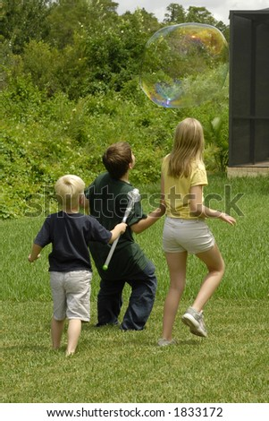 Children chasing a large soap bubble in the back yard. - stock photo