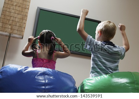 Children cheering on bean bags